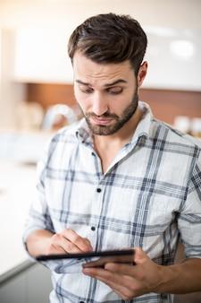 Zmieszany młody człowiek używa cyfrową pastylkę w kuchni