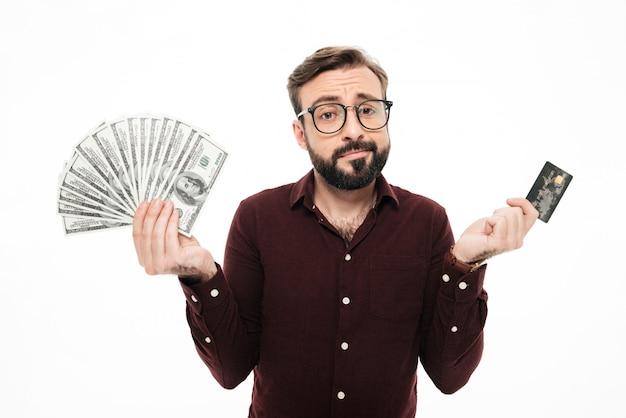 Zmieszany myślący młody człowiek trzyma pieniądze i kredytową kartę.
