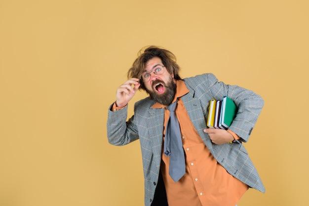 Zmieszany nauczyciel z książkami zły nauczyciel brodaty mężczyzna w garniturze edukacja z powrotem do szkoły portret