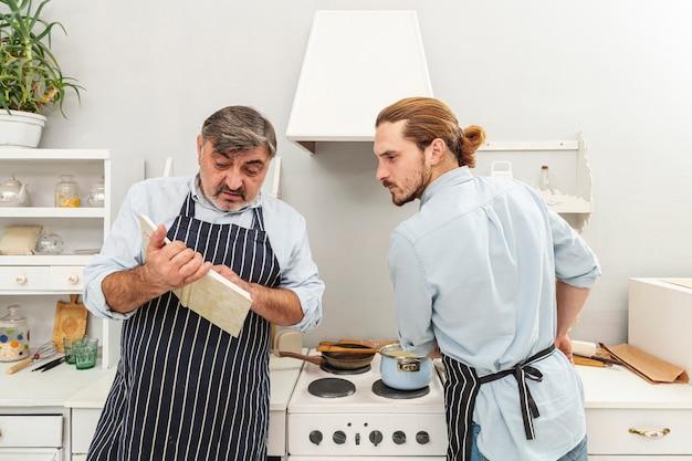 Zmieszany ojciec i syn patrzeje w książce kucharskiej