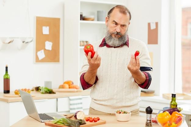 Zmieszany starszy mężczyzna gotuje