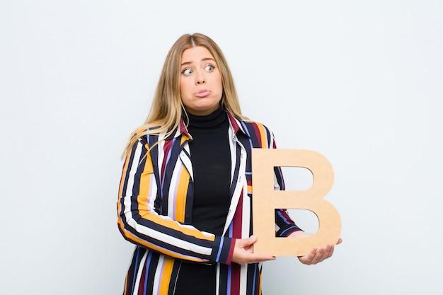 Zmieszany, wątpliwy, myślący, trzymający literę b alfabetu, aby utworzyć słowo lub zdanie.