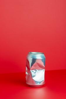 Zmięta aluminiowa puszka na czerwonym stole. bez plastiku. zanieczyszczenie środowiska. minimalizm. projekt.