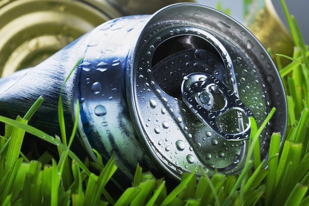Zmięta aluminiowa puszka na zielonej trawie