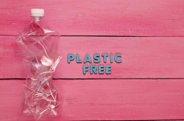 Zmięta butelka na czerwonej drewnianej powierzchni z tekstem bez plastiku