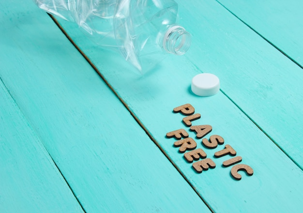 Zmięta butelka na niebieskiej drewnianej powierzchni z tekstem bez plastiku