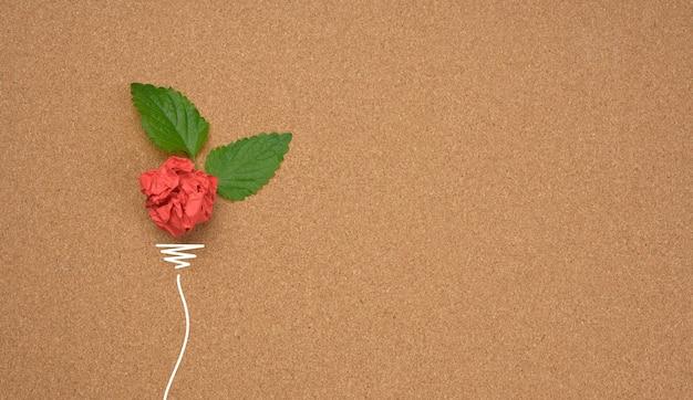 Zmięta czerwona kartka brązowego papieru i zielony liść na brązowym tle, kształt żarówki. koncepcja oszczędzania energii, nowy kreatywny pomysł, płaskie lay