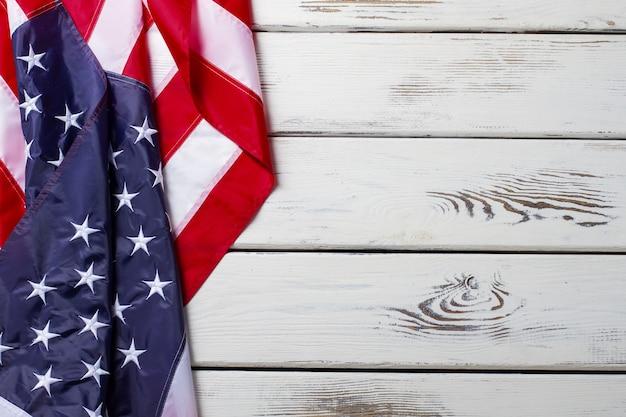Zmięta flaga amerykańska. amerykańska flaga na drewnianym tle. baner na białym stole. demokracja i wolność.