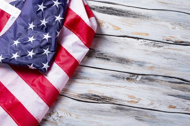 Zmięta flaga ameryki. amerykańska flaga na drewnianym tle. zachowaj prawa i wolności. kraina wielkich możliwości.