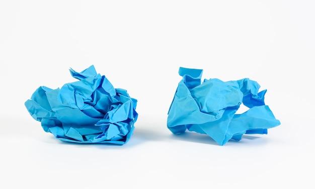 Zmięta kulka niebieskiego papieru na białym tle, element dla projektanta, z bliska