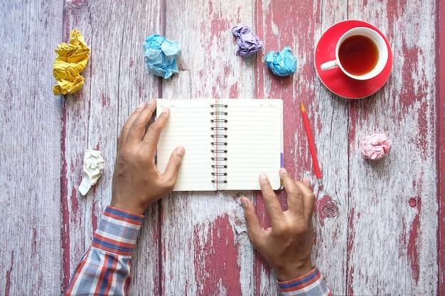Zmięta papierowa piłka i notatnik na drewnianym stole.