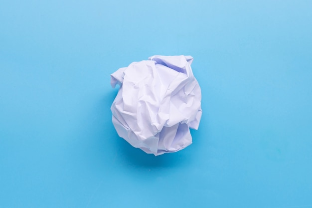 Zmięta papierowa piłka na błękita stole.