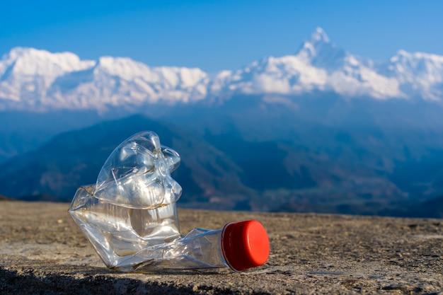 Zmięta pusta plastikowa butelka na tle pasma górskiego annapurna w himalajach. zanieczyszczenie środowiska w regionach turystycznych himalajów.