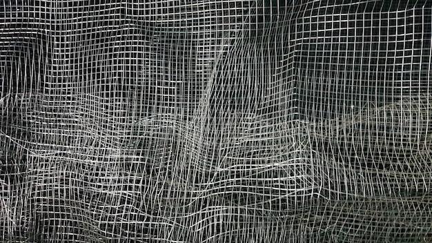 Zmięta siatka. abstrakcyjne tło. metalowa siatka z cieniem na czarnym tle. powierzchnia dużej rolki jest uszkodzona przez drucianą siatkę.