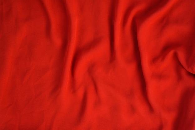 Zmięta tekstura jasnoczerwonej bezszwowej tkaniny.