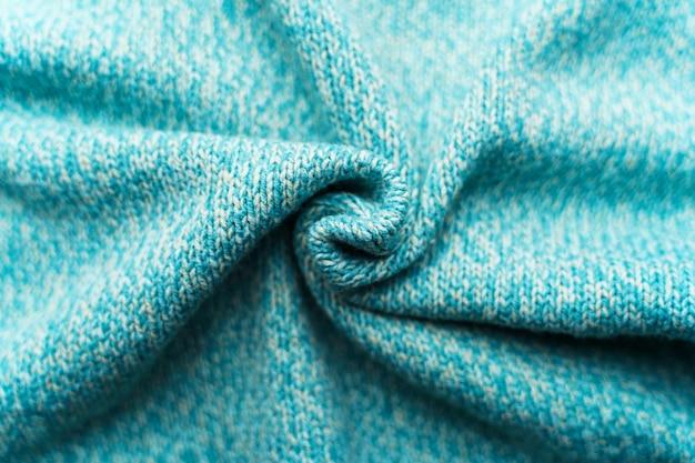 Zmięta tekstura niebieskiej turkusowej dzianiny. sweter w tle