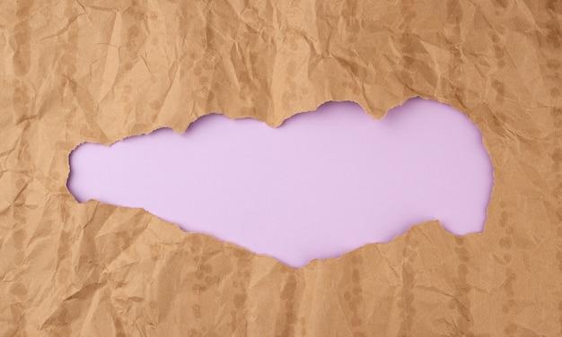 Zmięta tekstura papieru z brązowej kartki papieru z tłustymi plamami i dużą dziurą