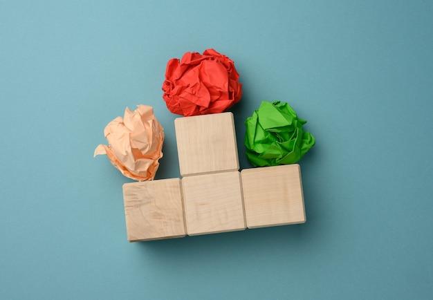 Zmięte arkusze kolorowego papieru na niebieskiej powierzchni. koncepcja poszukiwania rozwiązań, burza mózgów, znaczenie opinii, widok z góry