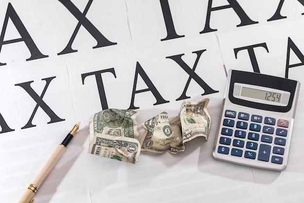 Zmięte dolary z długopisem i kalkulatorem na białym papierze