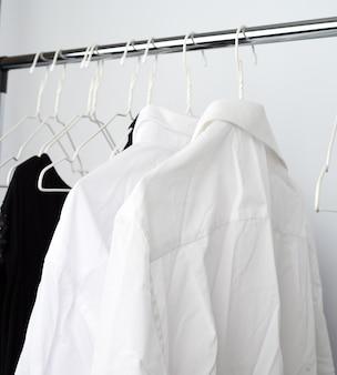 Zmięte koszule białego człowieka wiszące na metalowym wieszaku
