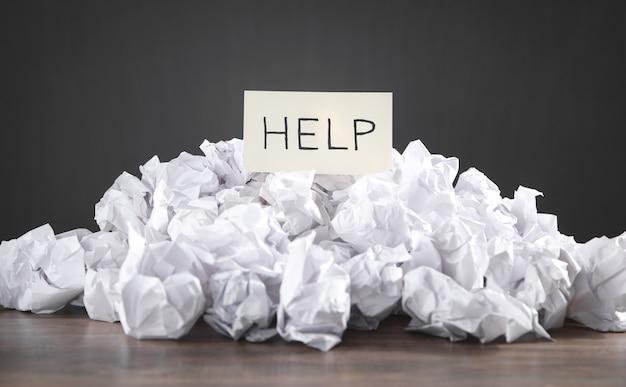 Zmięte kulki papierowe z napisem pomoc.