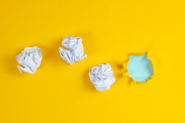 Zmięte kulki papieru, podarta dziura w żółtym papierze. widok z góry. minimalistyczna koncepcja biznesowa
