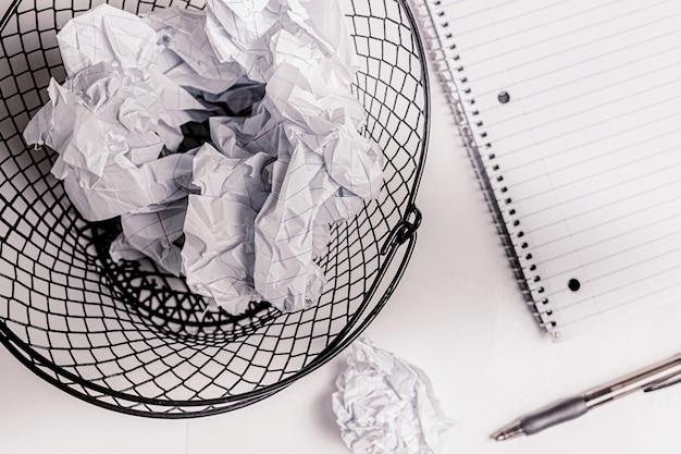 Zmięte papierowe notatki w przewodowym koszu na śmieci.