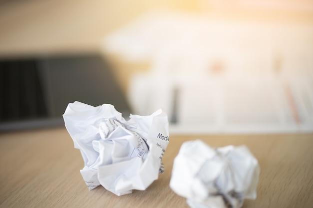 Zmięte papiery są na stole z nieudaną pracą. trudno jest stworzyć dobry pomysł na bu