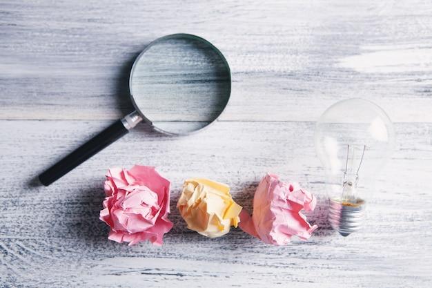 Zmięte papiery, żarówka i szkło powiększające
