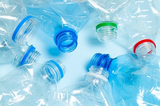 Zmięte plastikowe butelki na niebieskim tle. plastikowe śmieci.