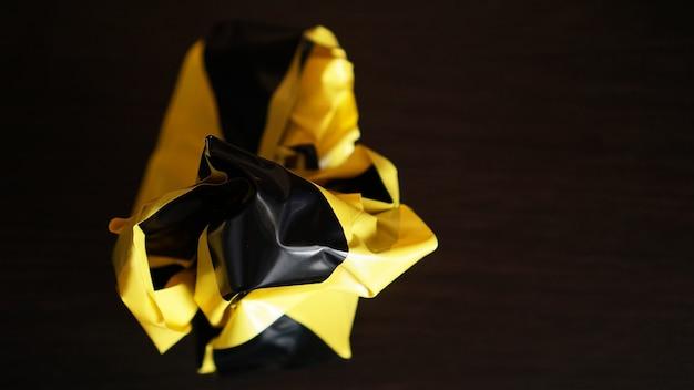 Zmięte żółto-czarne taśmy na ciemnym tle
