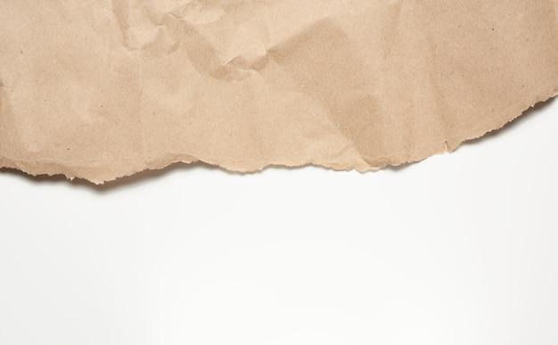 Zmięty arkusz brązowego papieru do pakowania na białym tle
