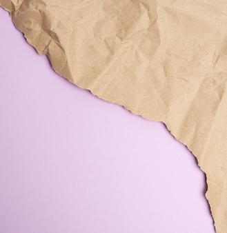 Zmięty arkusz brązowego papieru do pakowania na fioletowej przestrzeni