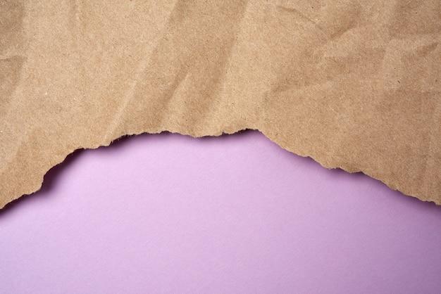 Zmięty arkusz brązowego papieru do pakowania z poszarpanymi krawędziami na fioletowym tle