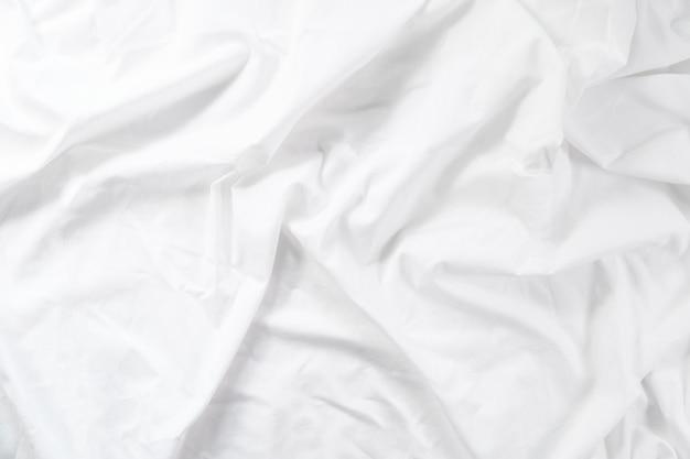 Zmięty arkusz. poranne łóżko biała tkanina.