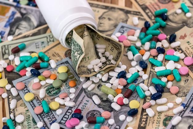 Zmięty banknot dolarowy i kolorowe pigułki