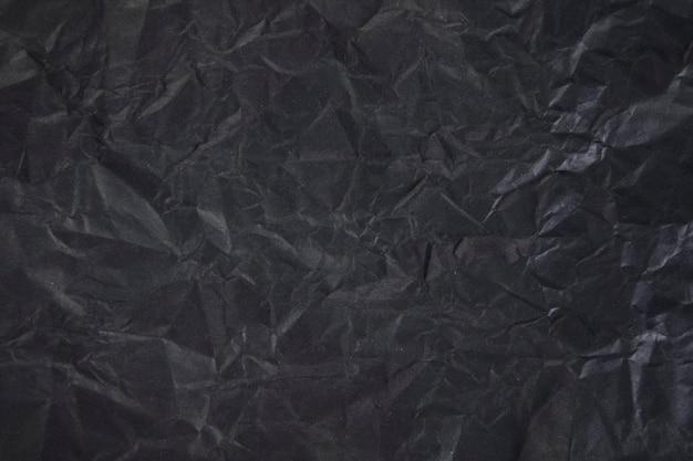 Zmięty czarny papier jako scena. ciemny ton