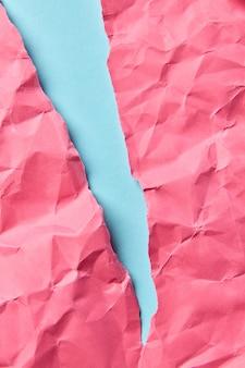 Zmięty gorący różowy papier na pastelowym niebieskim tle jako dekoracyjne tło dla twojej kreatywności z miejscem na tekst.