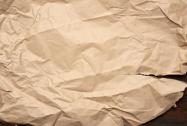 Zmięty i rozdarty brązowy kawałek papieru na drewnianym tle