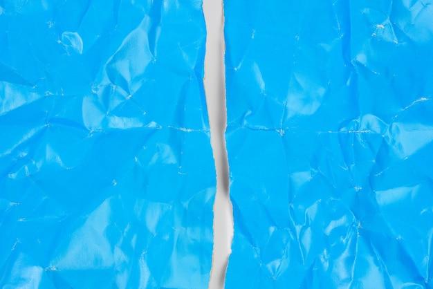 Zmięty niebieski karton papieru na białym tle, arkusz a4 rozdarty na pół