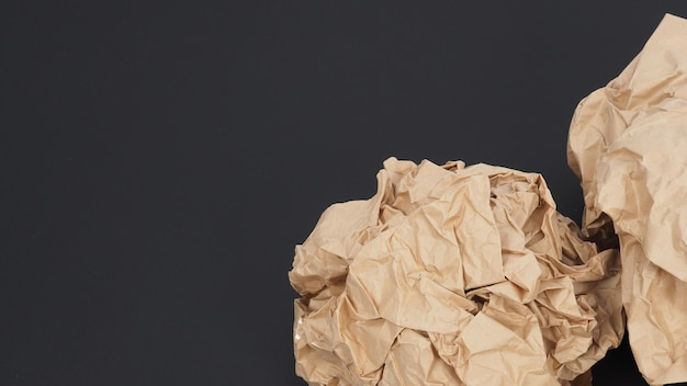 Zmięty papier brązowy. jest poturbowany na czarnym tle.