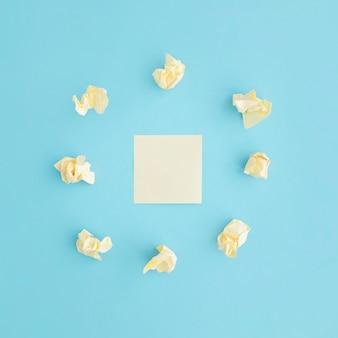 Zmięty papier otoczony pustą karteczkę na niebieskim tle