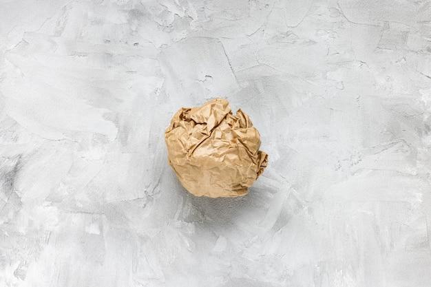 Zmięty papier pakowy brązowy na szarym stole