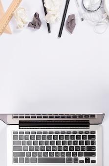 Zmięty papier z biurowymi dostawami i otwartym laptopem na białym tle