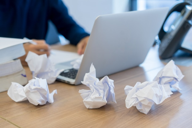 Zmięty papier z rozmycia pracownika człowiek ciężko pracuje po przeczytaniu projektu
