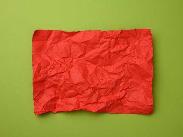 Zmięty prostokątny arkusz czerwonego papieru na zielonej powierzchni, widok z góry. miejsce na napis