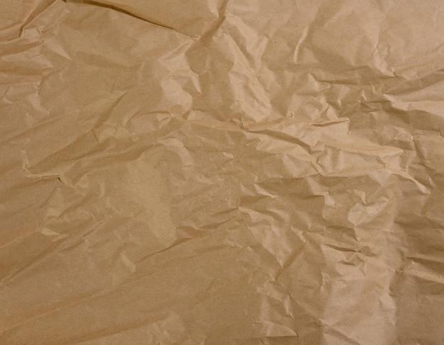 Zmięty pusty arkusz brązowego papieru pakowego, vintage tekstura dla projektanta, pełna klatka