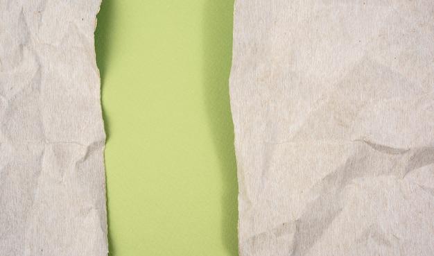 Zmięty szary karton papieru na zielonym tle, kopia przestrzeń