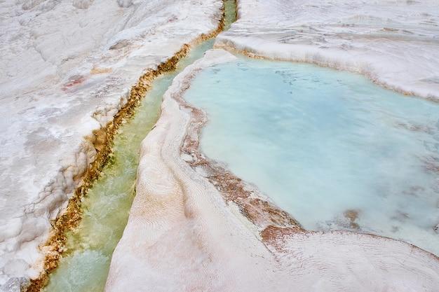 Zmineralizowana woda w uregulowanym kanale spływa na zbocze i tworzy kaskadę tarasowych wanien pokrytych śnieżnobiałymi stalaktytami kalcytowymi indyk pamukkale