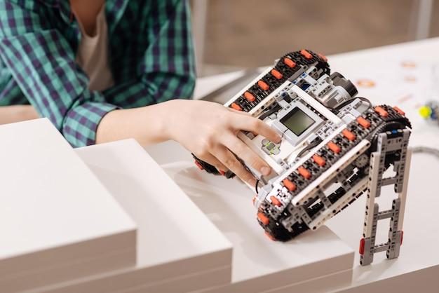 Zmodernizowane urządzenie. wprawny, bystry chłopiec siedzi w klasie, wyrażając zadowolenie i programując robota